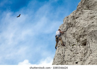 Man climbs to the top of the mountain. Rocks and blue sky. Bird in the sky and climbing wall.. To reach a top.