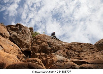 Man climing on huge rock wall