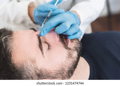 Man at clinic on facial treatment, fillers injection on glabella.