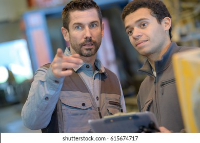 Man with clipboard giving instructions to younger colleague