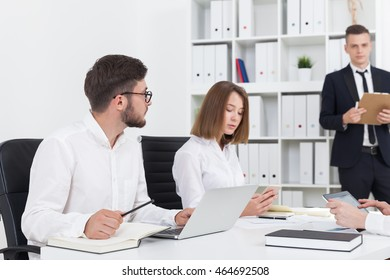 Man with clipboard standing making a report. His colleagues listening and taking notes with different gadgets. Concept of business talk, brainstorming