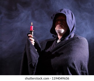 A man with a cloak and hood holds up a candleholder in the dark