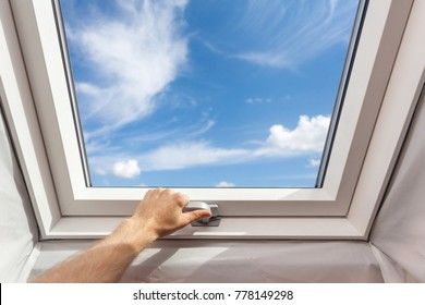 Man close new skylight (mansard window) in an attic room against blue sky