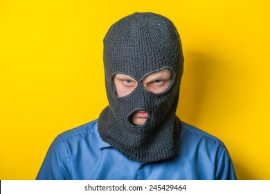 man close up thief in a mask and a blue shirt on a yellow background looks slyly to the camera. Mimicry. Gesture. photo Shoot/ evil criminal wearing balaclava