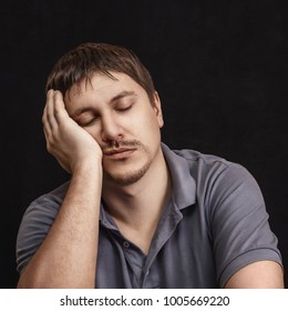 A man with closed eyes leans on his arm