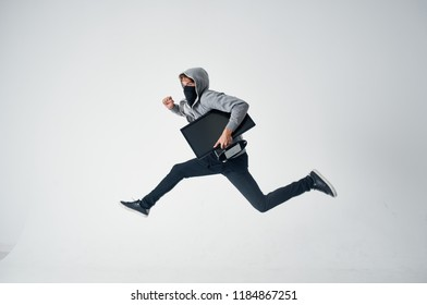 a man with a closed face in a hood steals a monitor