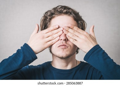The man closed his eyes with his hands. On a gray background.