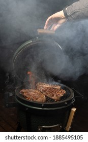 Man closes the lid of an egg type grill with a steaks inside. New york steak.