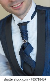 man closeup dressed up in wedding suite, tie with jewellery close up