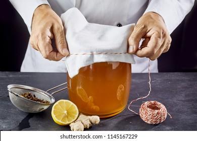 Man closing jar full of kombucha SCOBY tea with gauze bandage