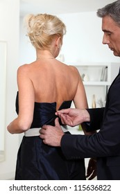 Man closing zipper  of his wife's dress