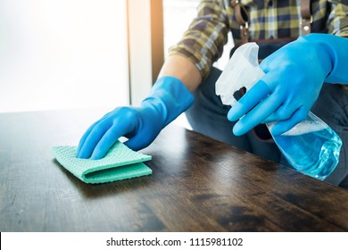 man with cloth cleaning wooden table in home uses rag and fluid in a spray
