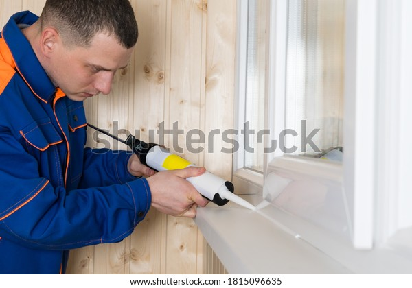 a man in clothes for repair seals the window cracks with selikon