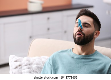Man with clothespin suffering from runny nose at home. Space for text
