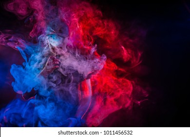 A man in a cloud of steam. Vaping man. A cloud of vapor. Vaping man holding a mod.