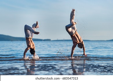 The man is a coach of capoeira and a boy practicing capoeira on the beach - concept about people, lifestyle and family sport. A man and a young man performing handstand in water