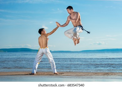 The man is a coach of capoeira and a boy practicing capoeira on the beach - concept about people, lifestyle and sport. Family sport