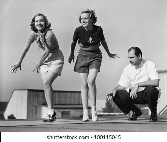 Man coaching two female dancers