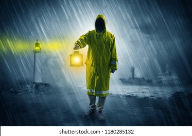 Man at the coast coming in raincoat with glowing lantern concept