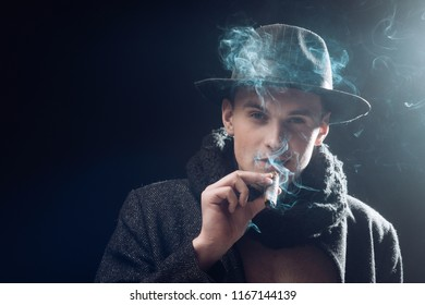 Man in coat, hat smoking cigar, dark background. Macho on mysterious face, detective, investigator, agent. Guy in old fashioned outfit looks mysterious with cigar and smoke. Vintage detective concept.