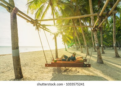 Man with coconut relaxing on the beach between palms. Vacation concept.
