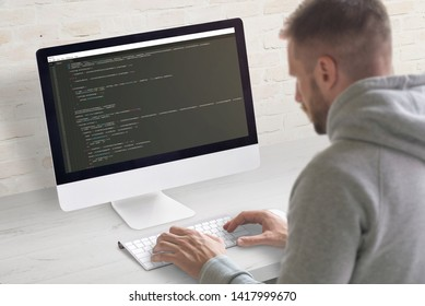 Man coding app on a computer. Close-up scene. Clean office desk with brick wall in background.