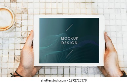 Man in a coffee shop using a tablet mockup