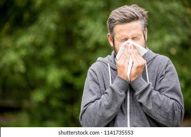 Man with cold or hay fever sneezing using tissue to clean nose