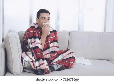 A man with a cold sits on the couch, hiding behind a red rug. He blows his nose in a white kerchief. He has a cold