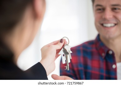 Man Collecting Keys To New Home From Female Realtor