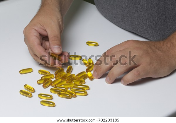 The man collects pills of yellow color from the table.