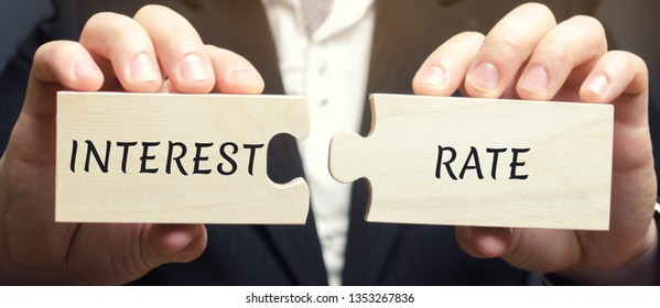 A man collects wooden puzzles with the word Interest Rate. The amount of money in the form of interest, which is paid by the borrower in favor of the lender for the use of assets. APR