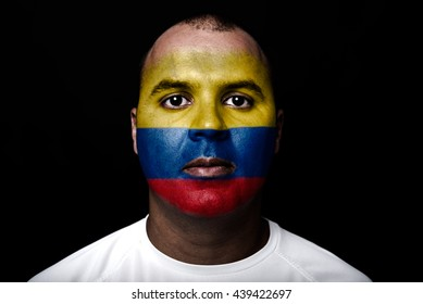 Man with Colombia flag painted on  his face on black background