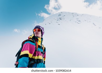 man in a colored suit with a backpack and glasses stands against the background of the mountains