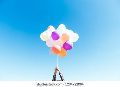 man with colorful balloons in beautiful sky