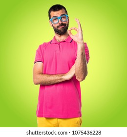 Man with colorful clothes making OK sign