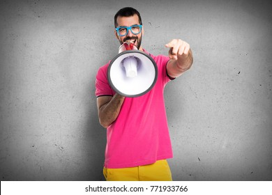 Man with colorful clothes shouting by megaphone