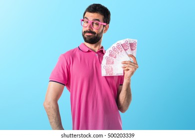 Man in colorful clothes taking a lot of money over colorful backgound