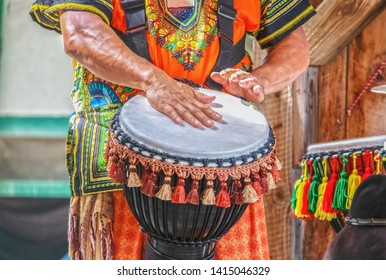 Man in colorful costume plays African ethnic percussion drum with tassels against blurred background - cropped and motion blur on hands