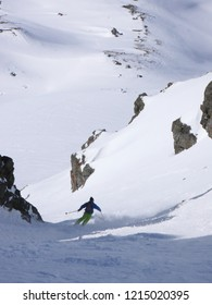 man in colorful outfit skiiing down a very steep snow couloir under a cable car station in the Swiss Alps in deep winter