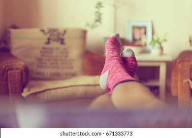 Man in colorful socks, relaxing on chair in bedroom, first person view, toned.