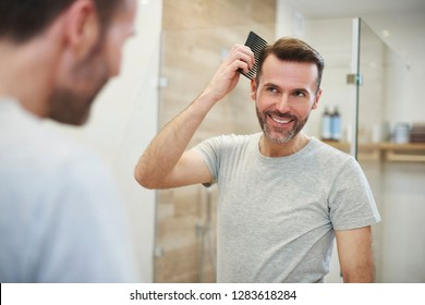 Man combing his hair in the bathroom