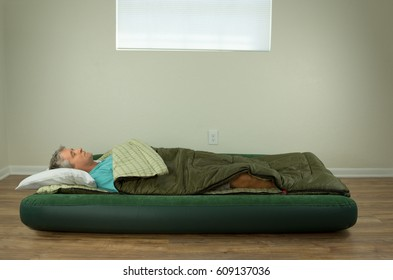 Man comfortably sleeping on blow up air mattress bed in sleeping bag with clean walls and window in the background.