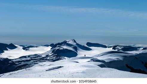 Man coming over the hill, seen from Glittertind. Galdhopiggen behind. Jotunheimen, Norway.