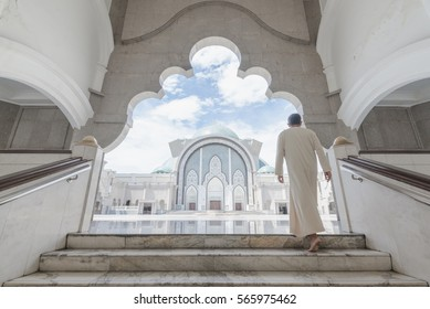 a man coming up the stairs , in mosque
