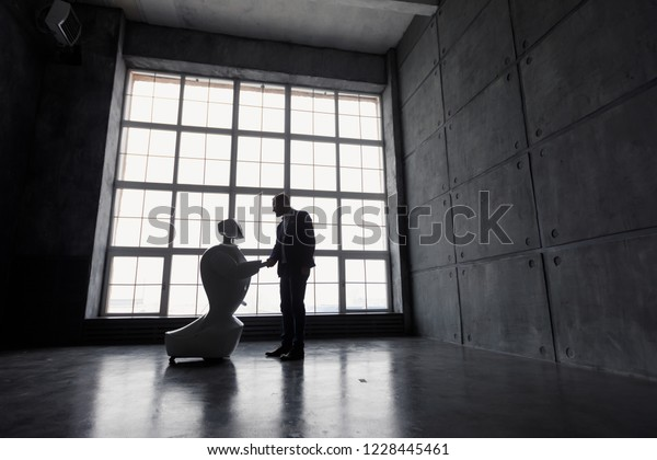 A man communicates with a robot, with cardboard box in hand. delivery concept. silhouette of the robot against the window