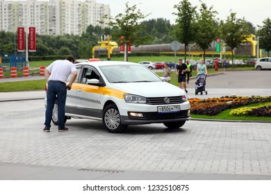 The man communicates with the taxi driver, who is driving white, Volkswagen brand. Moscow. 27.08.2018