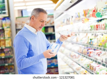 Man comparing products at the supermarket
