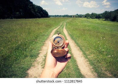 Man with compass in hand on rural road. Travel concept