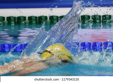Man compete in swimming pool. Man swimming freestyle. Swimmer in swimming pool behind the water splash curtain.